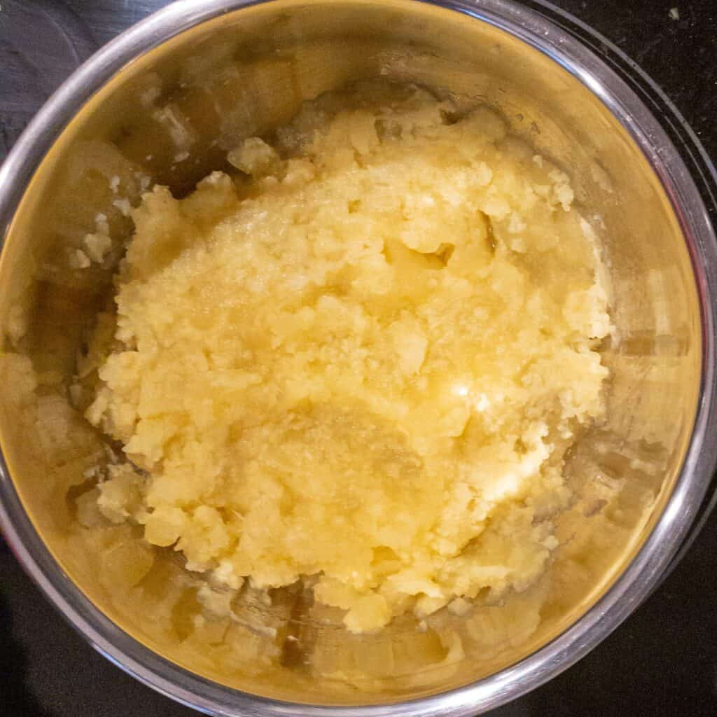 Close up showing potatoes and cauliflower mashed after being boiled