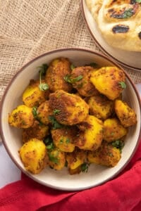 Bowl of Bombay Potatoes with Naan on the side