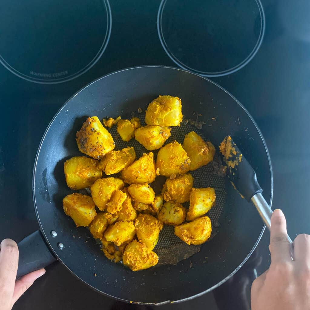 Spiced potatoes being pan fried