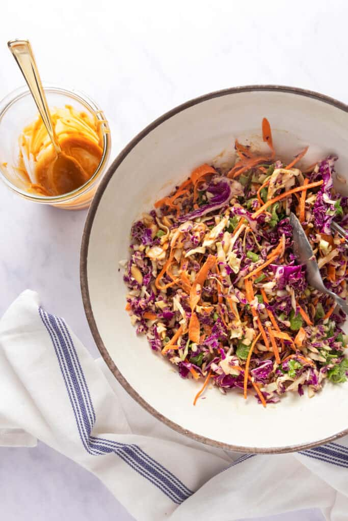 Mixed slaw in a large bowl with an empty bowl of peanut dressing on the side