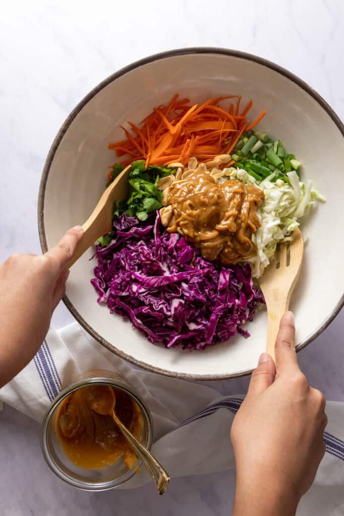 Hands mixing the bowl of summer slaw with peanut dressing