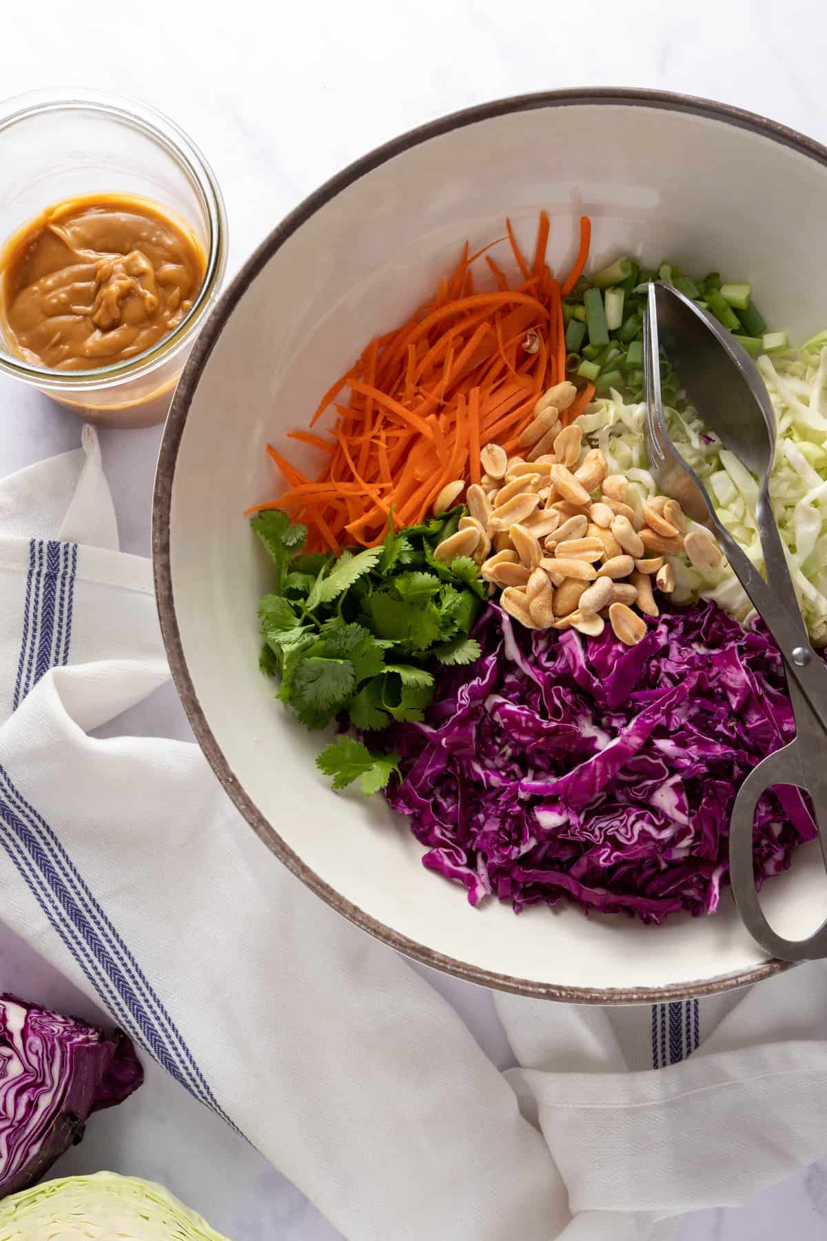 Bowl of all ingredients needed to make Asian summer slaw, with tons and a peanut dressing on the side