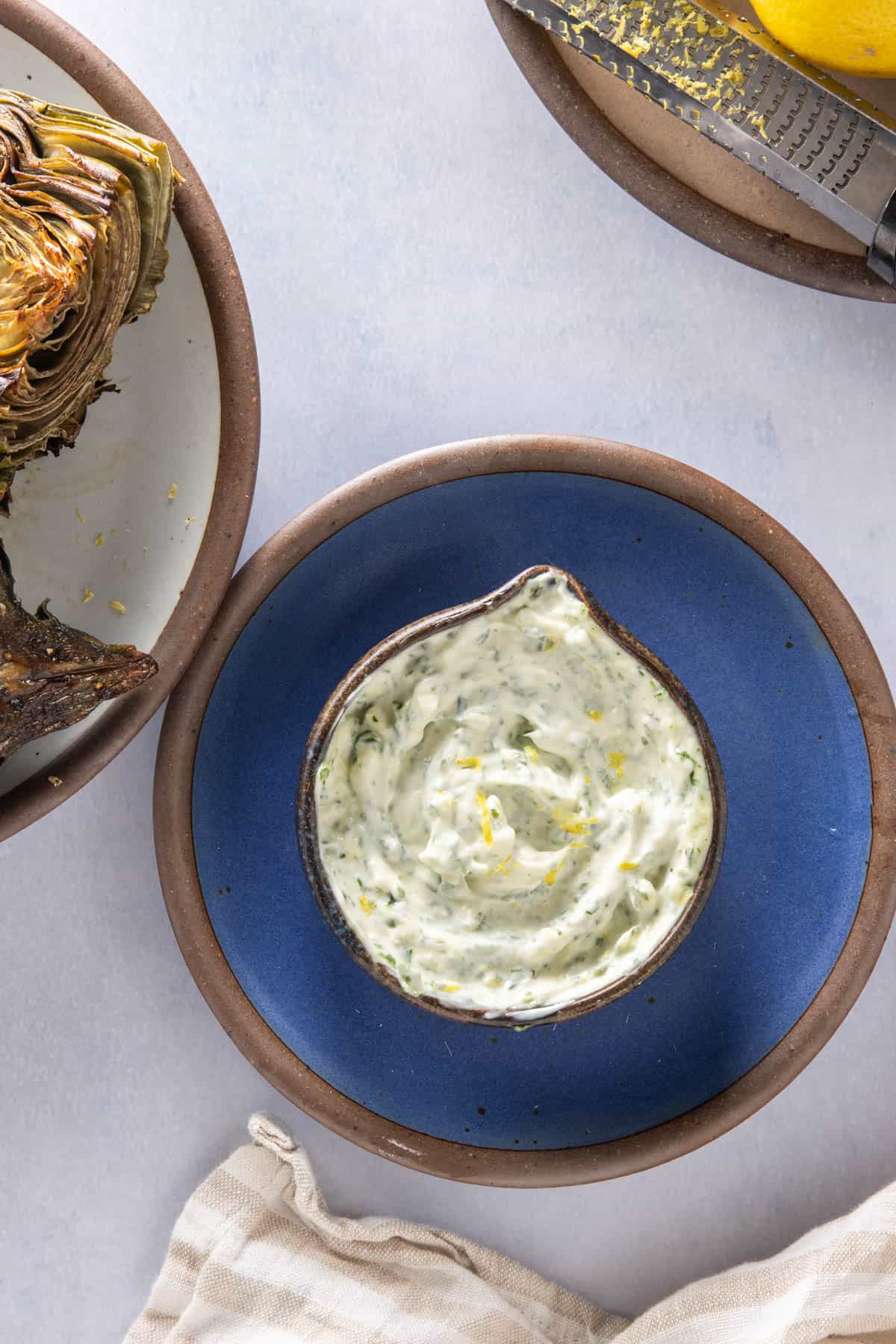 Jar of basil aioli on a plate with some artichokes and lemon zest in the background