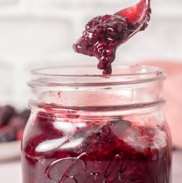 Close up of a spoonful of compote dripping back into the jar