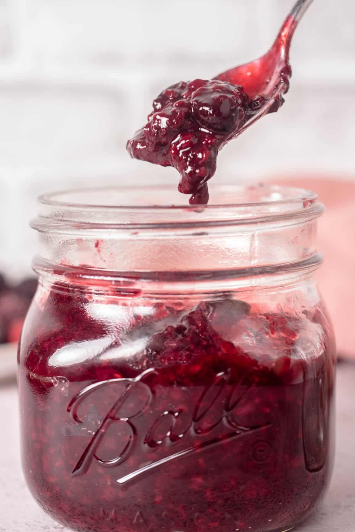 Close up of shot of berry compote with a spoon of it over the jar