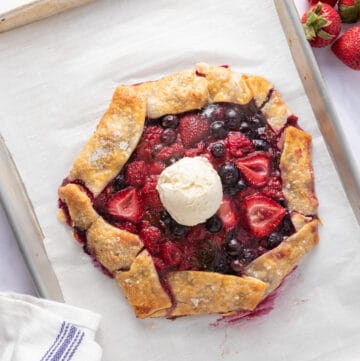 Baked berry galette in sheet pan with a scoop of icecream in the middle