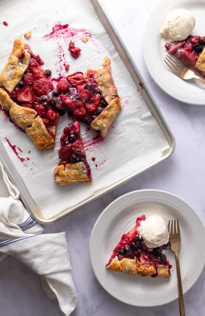 Slice of berry galette with vanilla ice cream next to sheet pan with rest of galette