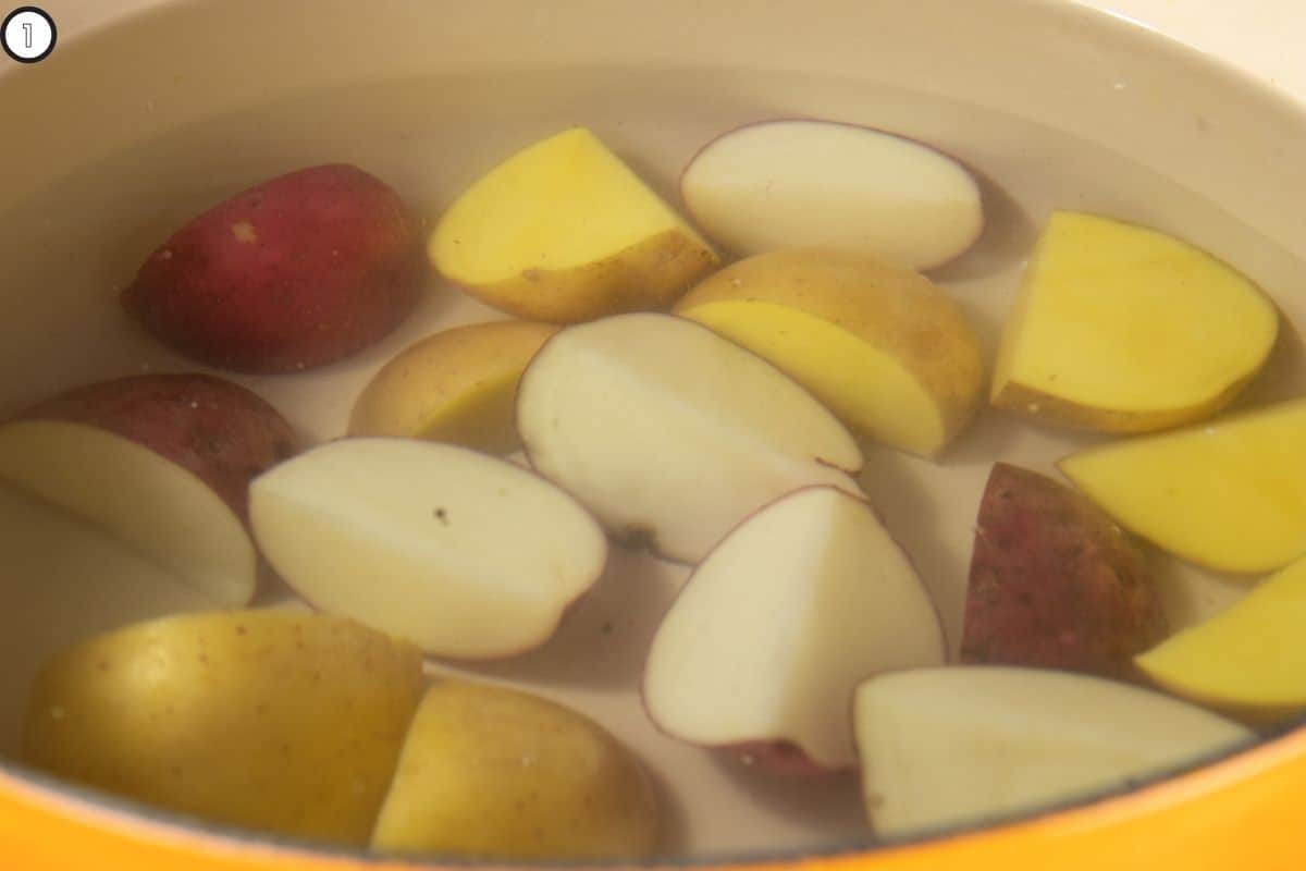 Close up of pot with quartered potatoes ready for boiling