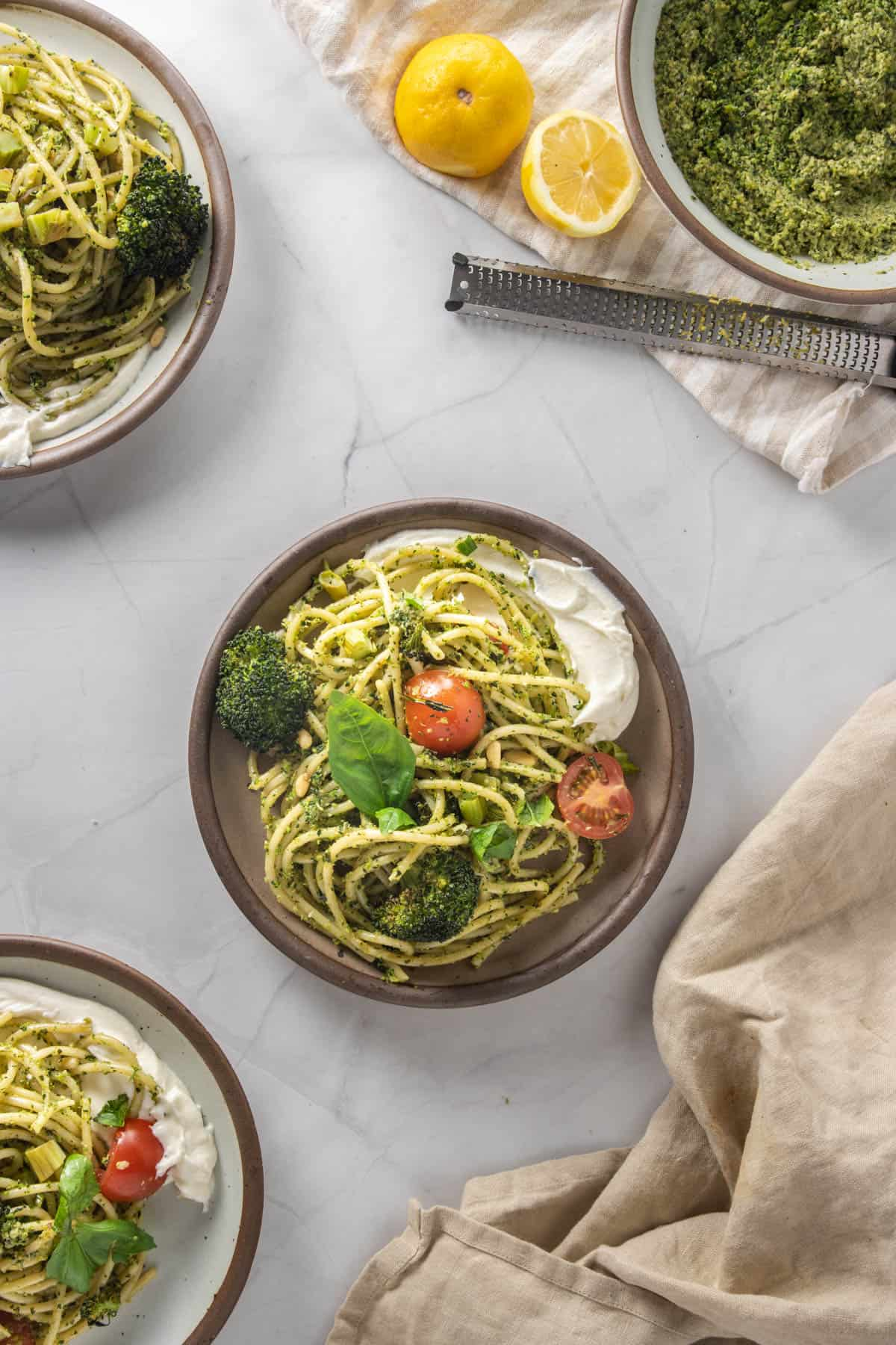 Plate of pasta with whipped ricotta in the center, several other plates and extra pesto in the background