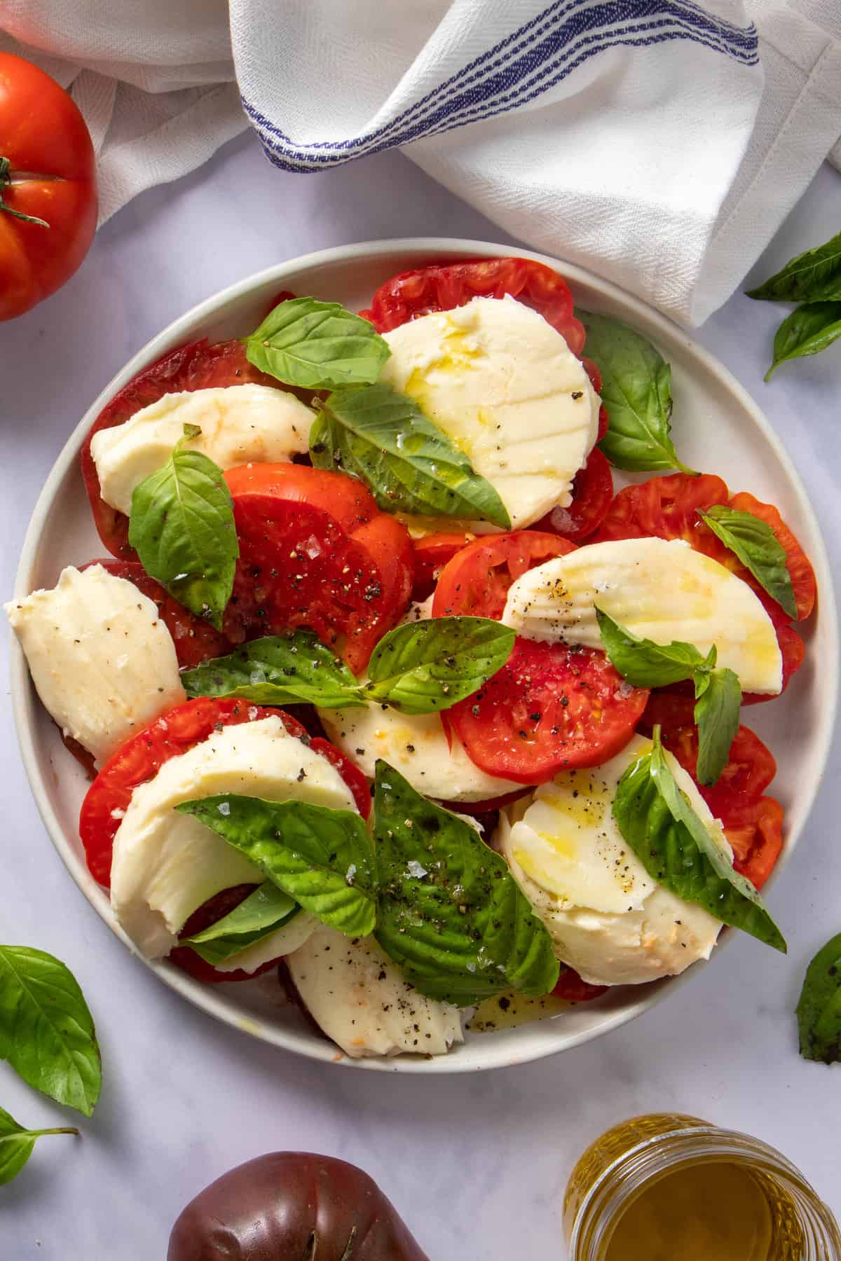 Plate with caprese salad (tomato, mozzarella and basil with olive oil, salt and pepper) as well as some garnishes on the side