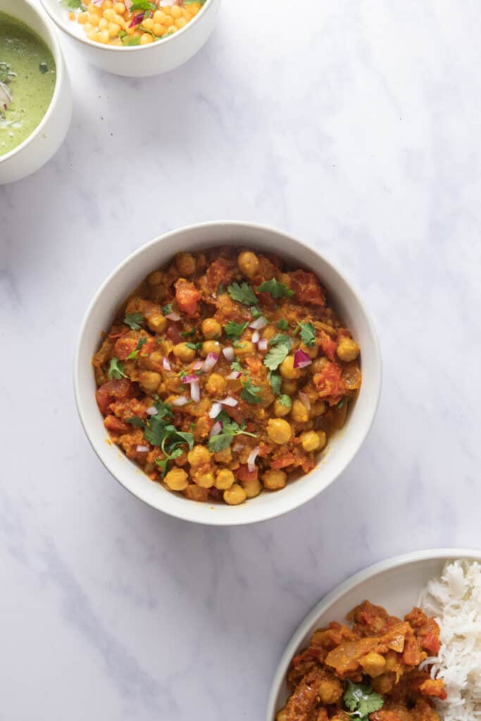 Close up of bowl of chana masala with some rice and yogurt in the background