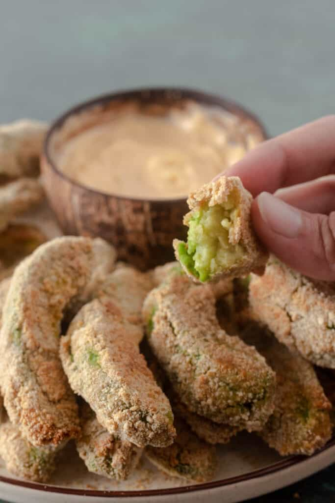 Close up of avocado fries, with a bite taken out, showing soft inside and crispy outside