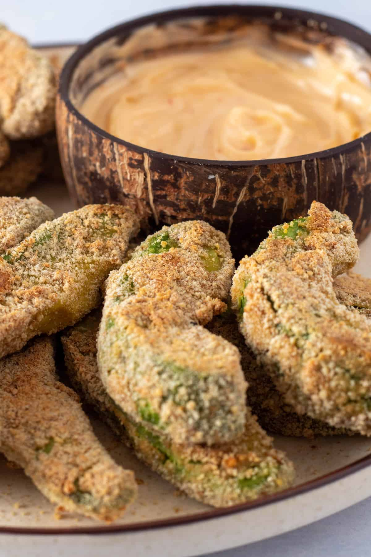 Close up shot of avocado fries showing the texture when it's done baking, as well as a dipping sauce in the background