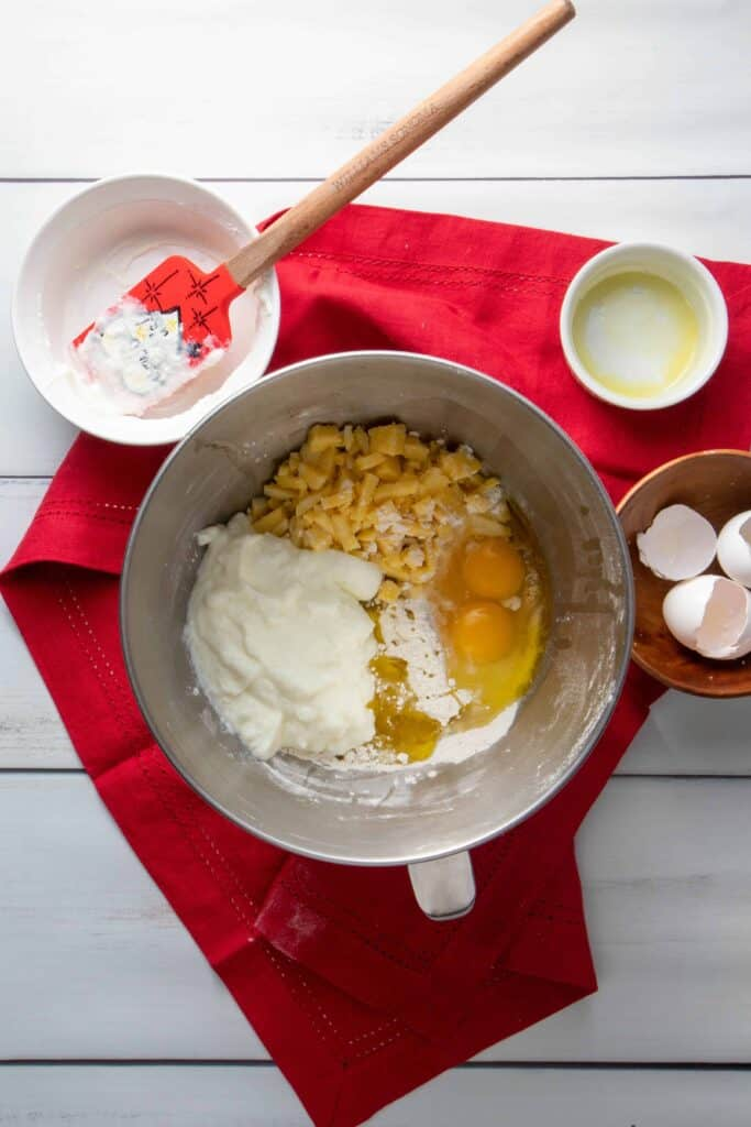 Eggs, cheddar, yogurt and oil poured on top of mixed dry ingredients