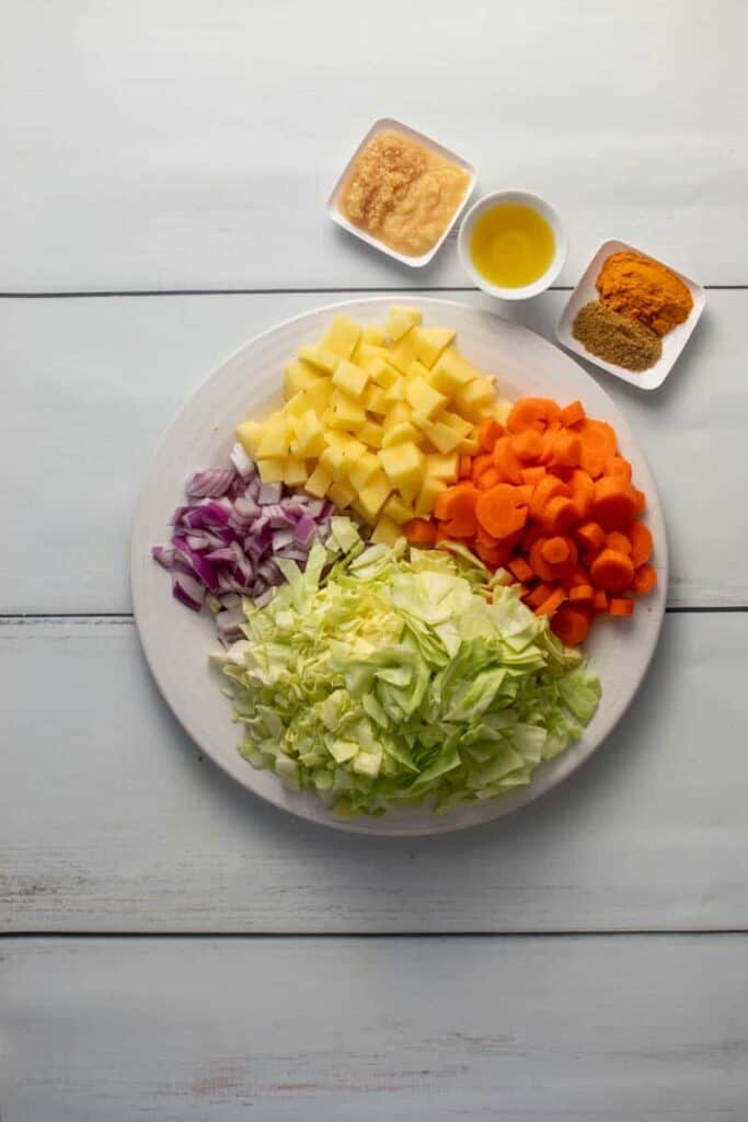 Ingredients needed for Ethiopian Cabbage stew include cabbage, carrots, onions, potatoes. Olive oil, ginger paste, garlic, turmeric and cumin.