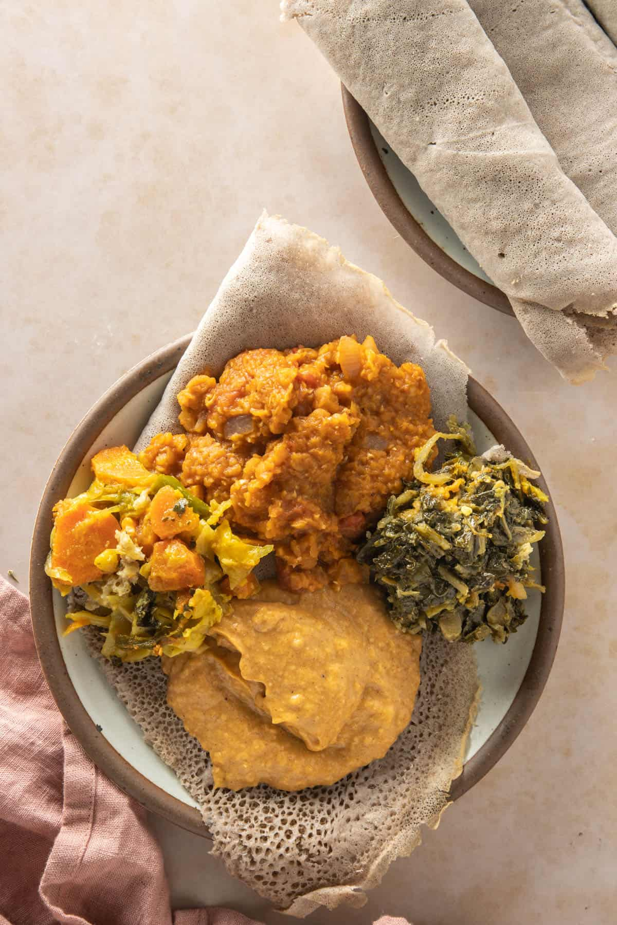 Plate of injera topped with different Ethiopian vegan dishes, including Misir Wot
