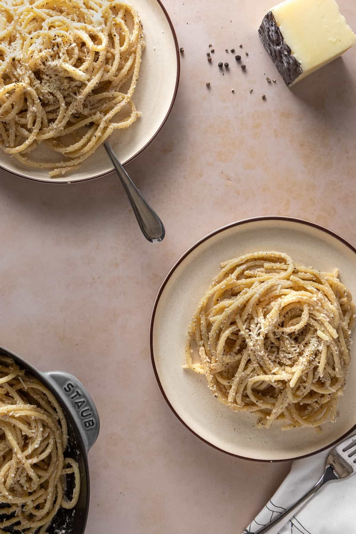 Two plates of cacio e pepe with the rest in the background along with some pecorino cheese