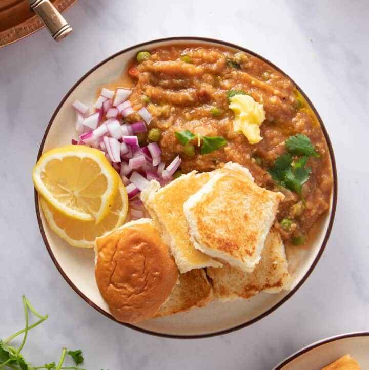 Plate of pav bhaji with rolls, bhaji, red onions, lemon wedges and garnished with cilantro