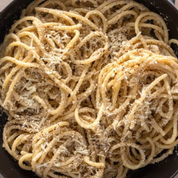 Close up of bowl of cacio e pepe showing the cheese and pepper garnished pasta