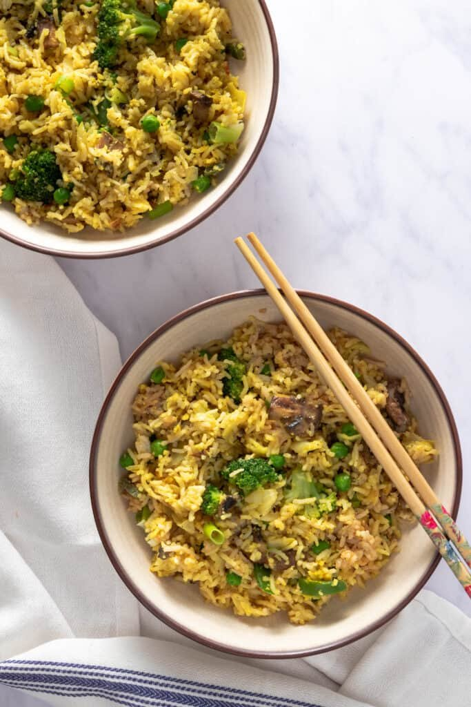 Bowl of vegetarian fried rice with chopsticks, and a second bowl in the background
