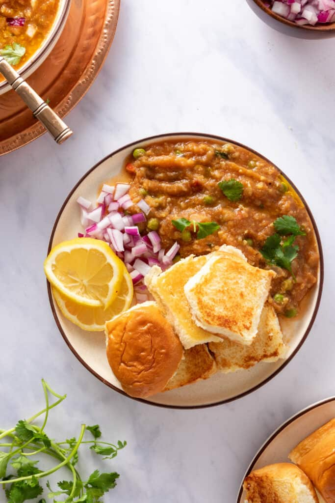 Plate with pav rolls, bhaji masala, red onions, and lemon wedges with some garnishes on the side