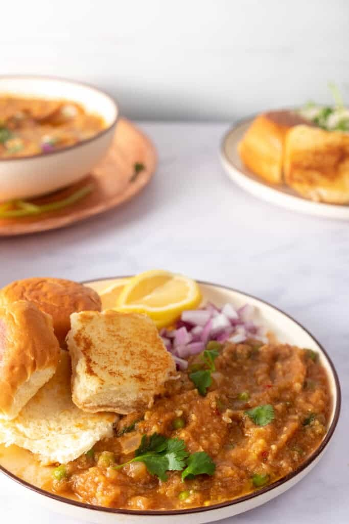 Close up showing toasted pav and bhaji on a plate, with extra pav and bhaji in the background