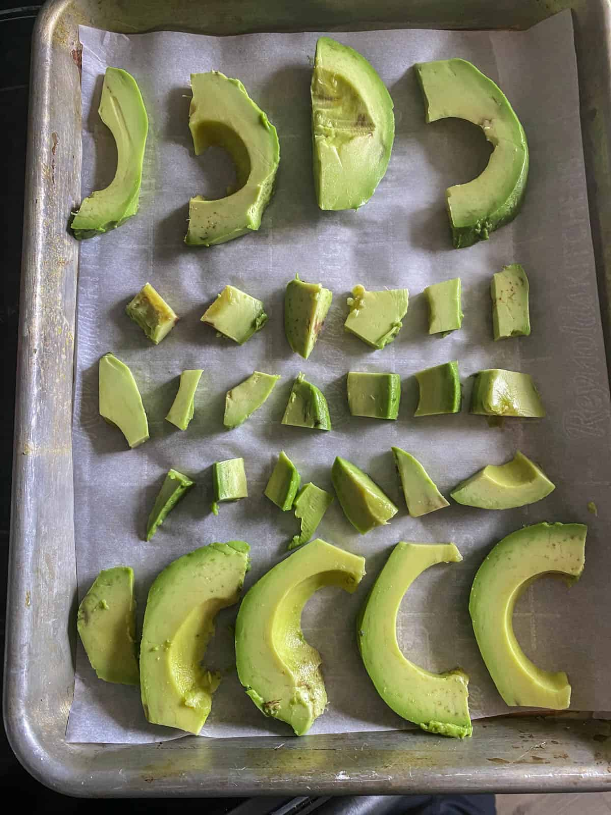 Baking sheet with slices and cubes of avocado