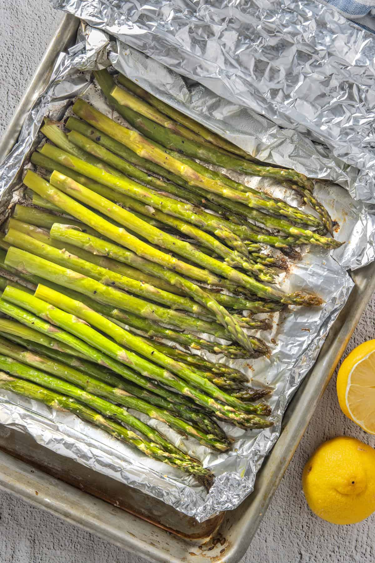 Roasted asparagus in foil, with lemons on the side