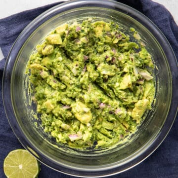 Close up of bowl of guacamole on a blue napkin
