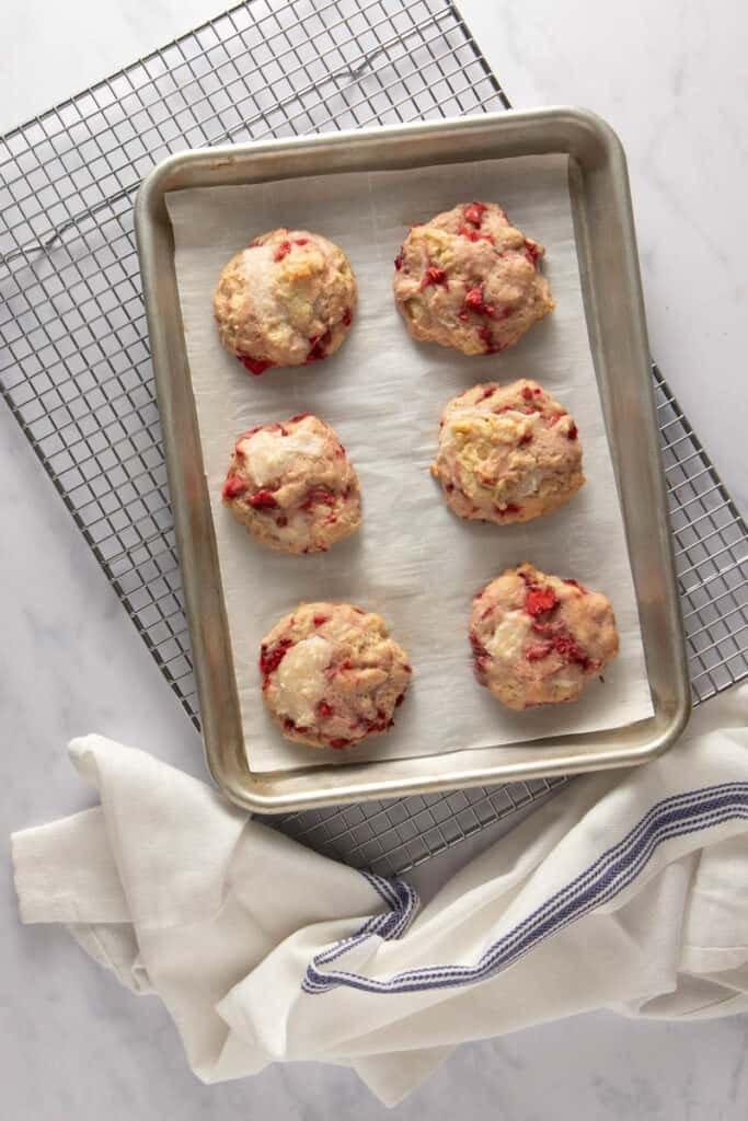 Strawberry cookies, filled with cream cheese filling, straight from the oven on a baking sheet, on top of a drying rack