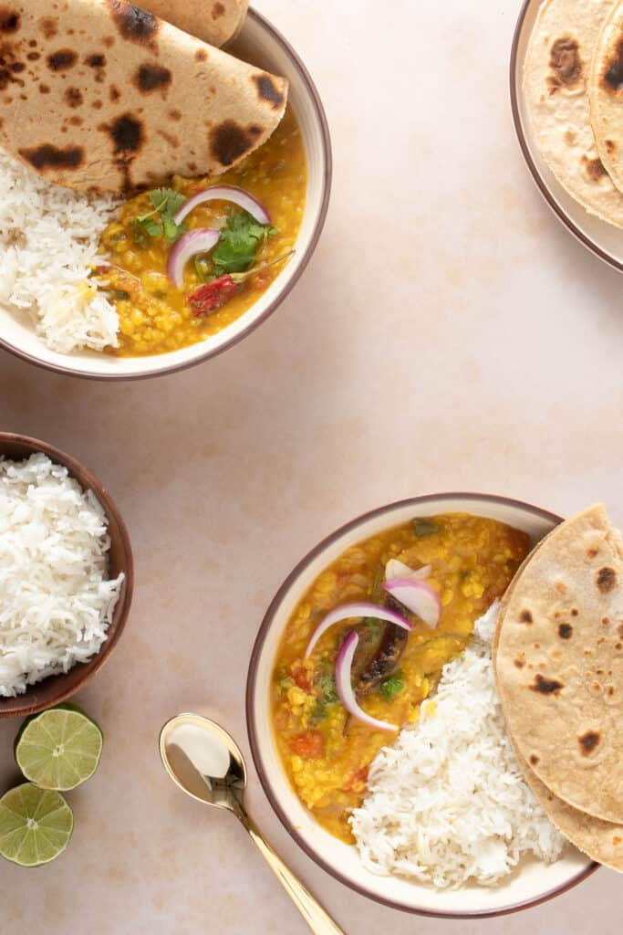Two plates with dal tadka, rice and roti (bread) along with a bowl of rice and a plate of extra rotis on the side