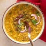 Close up of bowl with dal tadka showing all the garnishes