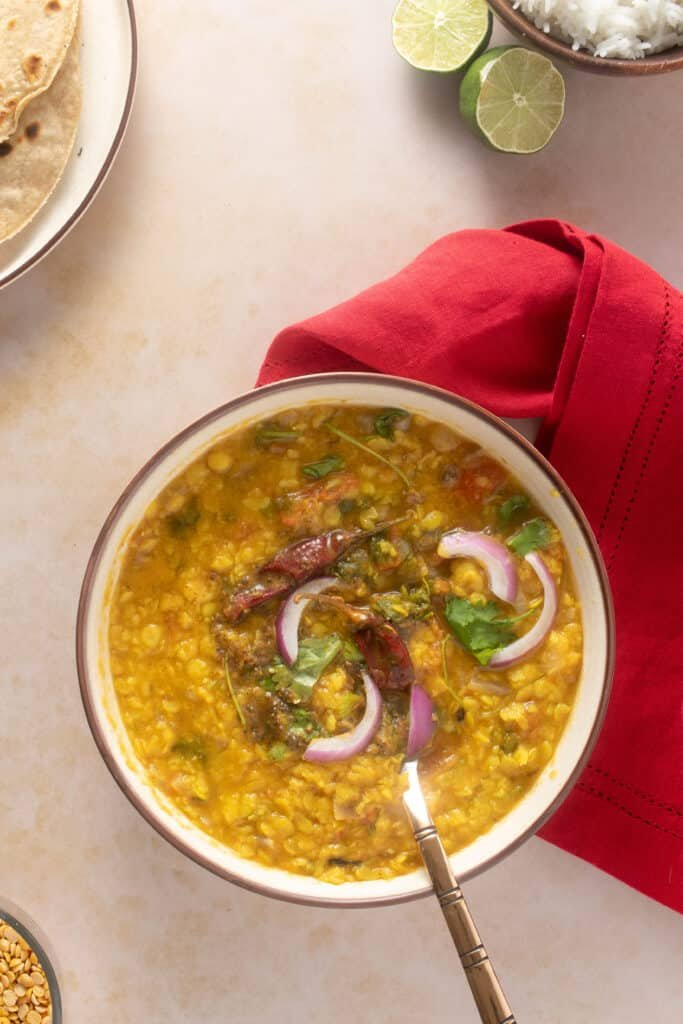 Bowl containing dal tadka - garnished with some red onions. Roti (bread) and rice are also visible in the corner