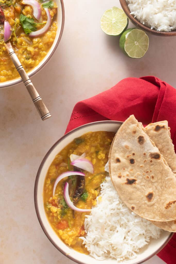 Bowl of dal tadka with rice and roti, as well as the bigger bowl and a bowl of rice in the background