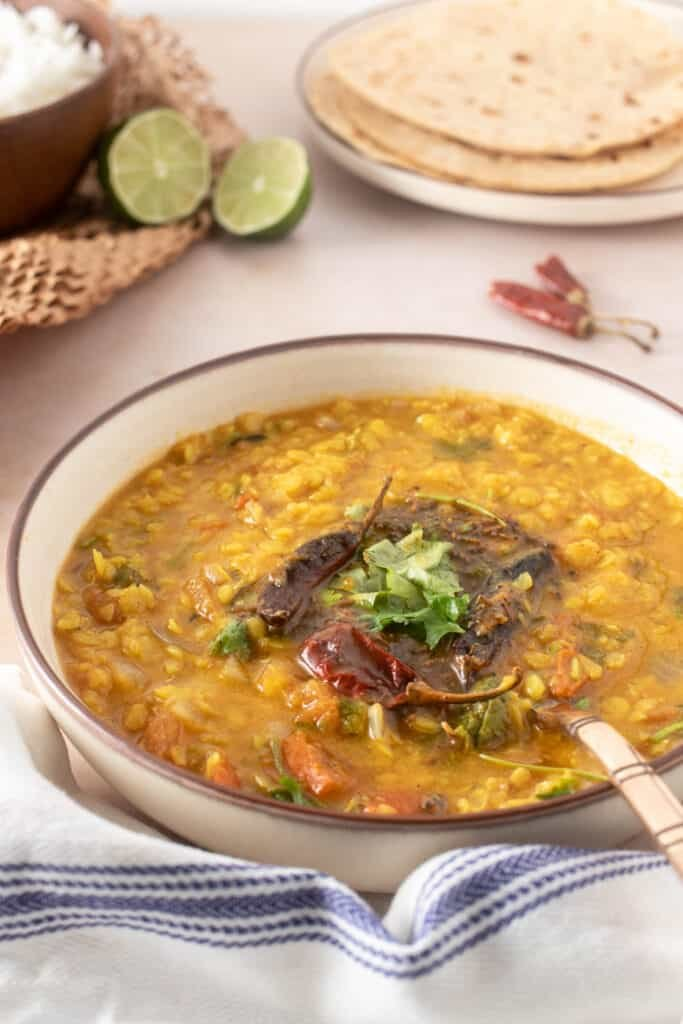 Side view of dal tadka showing the details of garnish - rice and bread in the background