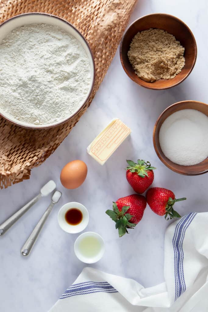 Ingredients needed for a strawberry shortcake cookie - flour, butter, brown and granulated sugar, baking powder, salt, vanilla, lemon juice and strawberries all laid out on a table