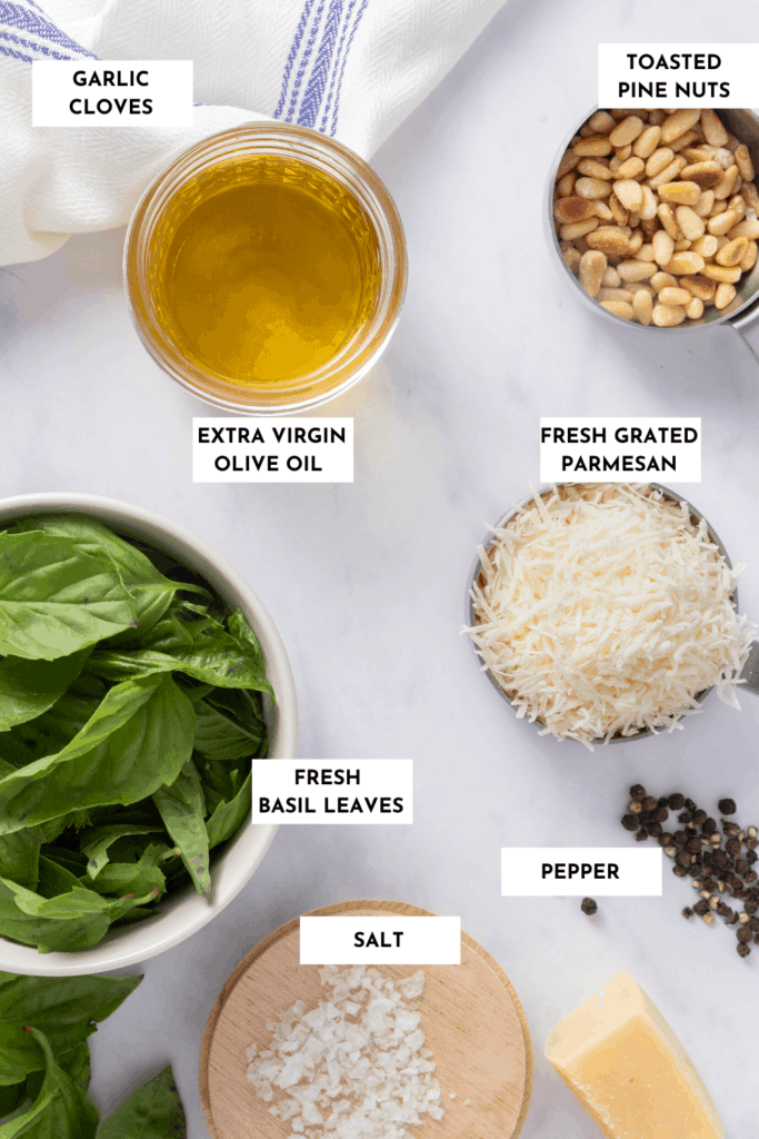 Ingredients labeled on a table - basil, olive oil, salt, pepper, parmesan and garlic (not pictured)