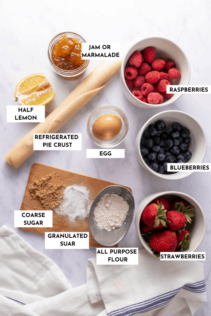 Ingredients for berry galette laid out on a table - berries, pie crust, sugar, flour, lemon juice, jam, and egg