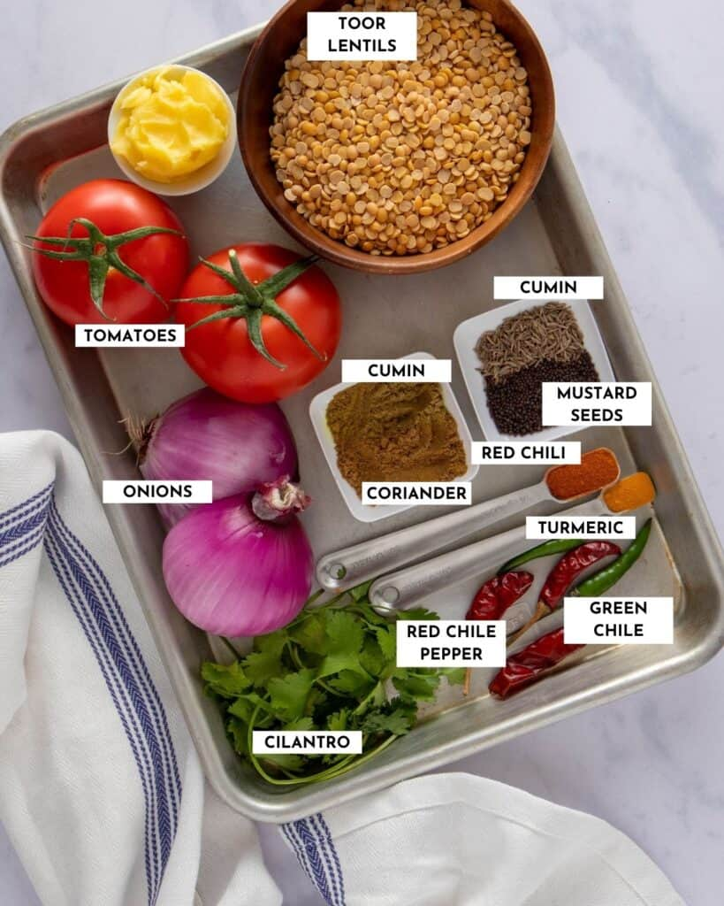 Platter showing all the ingredients needed to make dal tadka - lentils, tomatoes, ghee, red onions, cumin and coriander powder, cumin and mustard seeds, turmeric, red chili powder ,and Thai green chili peppers