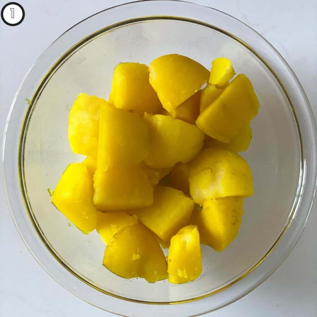 Peeled, parboiled potatoes to show how turmeric infuses in the potatoes when you add to boiling water
