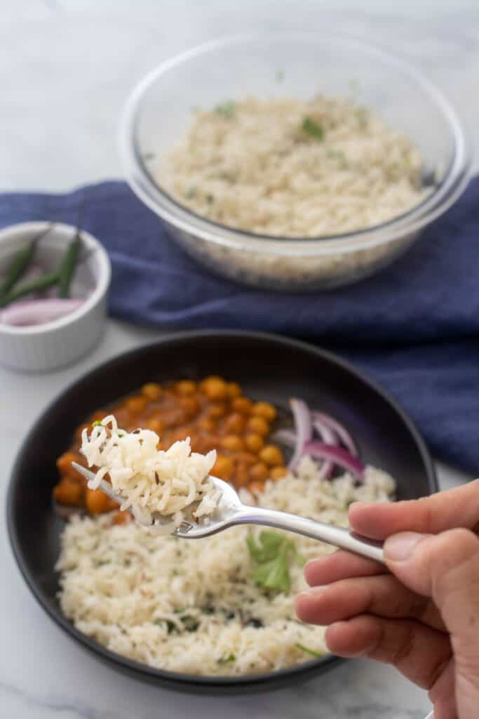 Close up of fork holding up jeera rice