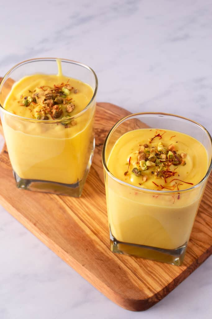 Two glasses of mango lassi with garnishes of pistachio and saffron on a wooden board
