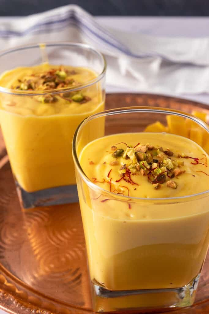 Two glasses of mango lassi with garnishes of pistachio and saffron on a copper plate