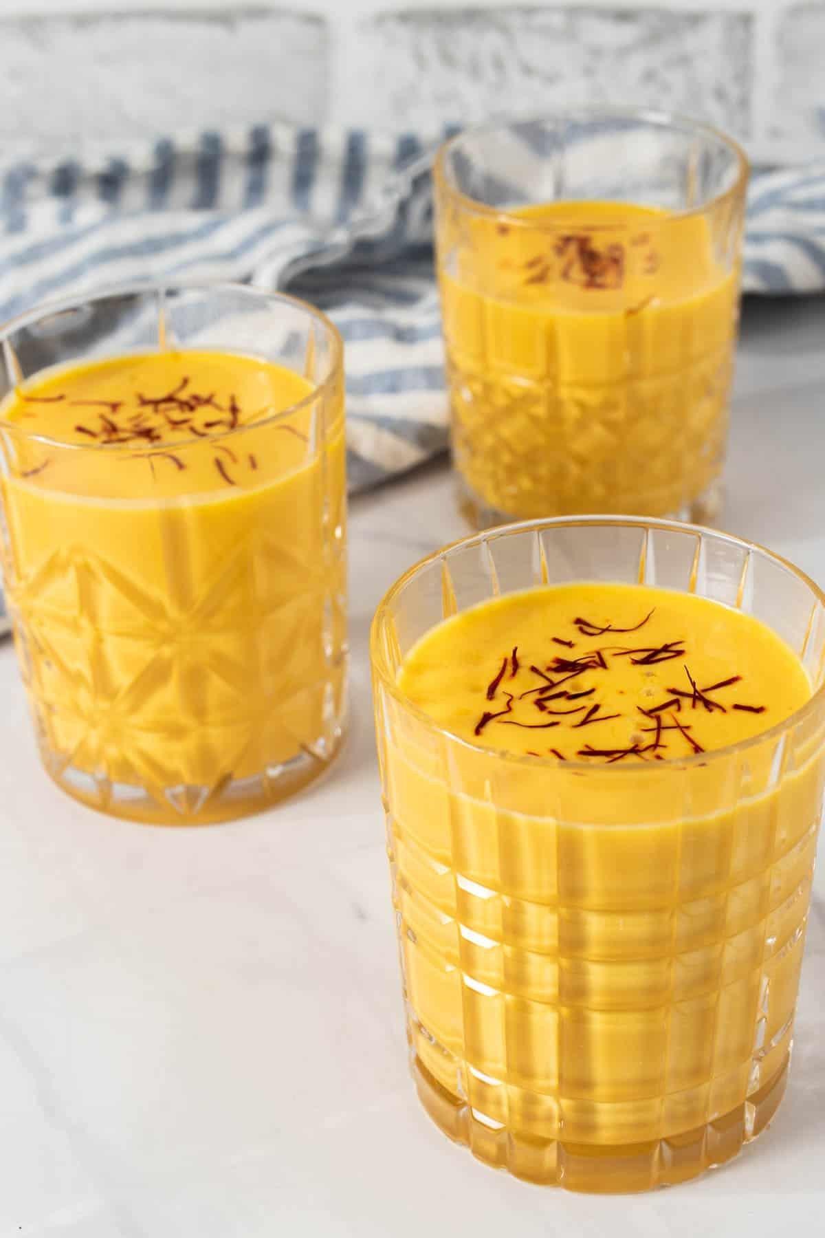 Three glasses of mango lassi with saffron garnish