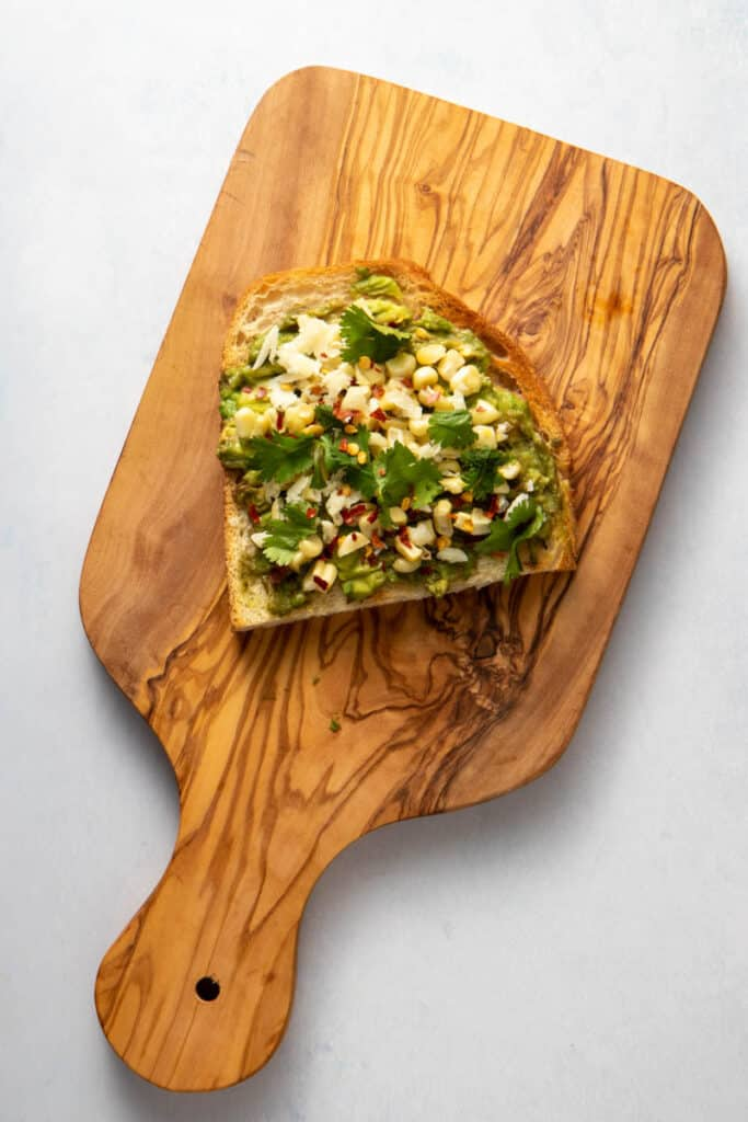 Avocado toast with corn, cilantro and cotija cheese on a wooden board