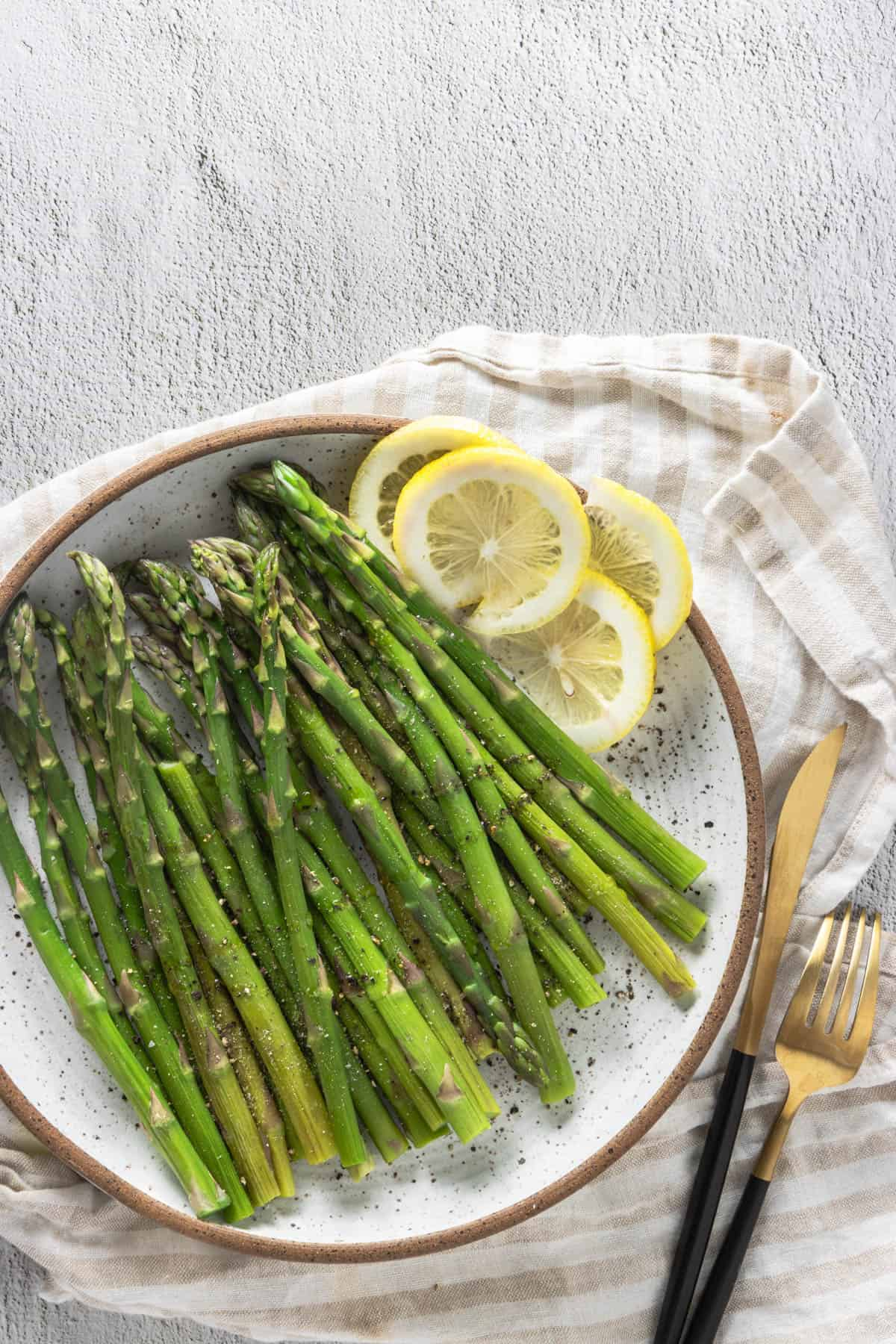 Cooked asparagus on a plate with some lemon slices for garnish