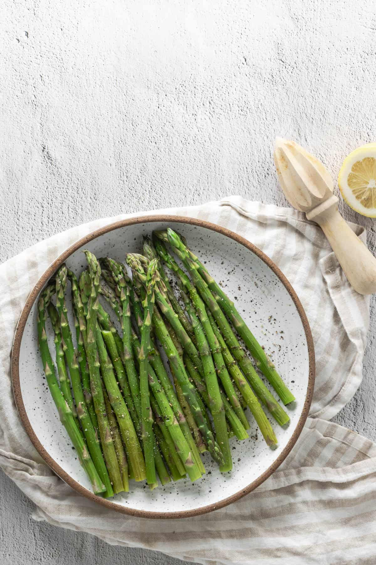 Finished plate of asparagus with lemon on the side