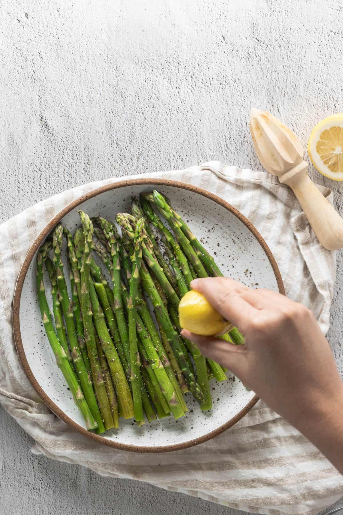 Hand squeezing lemon juice on microwaved asparagus on plate
