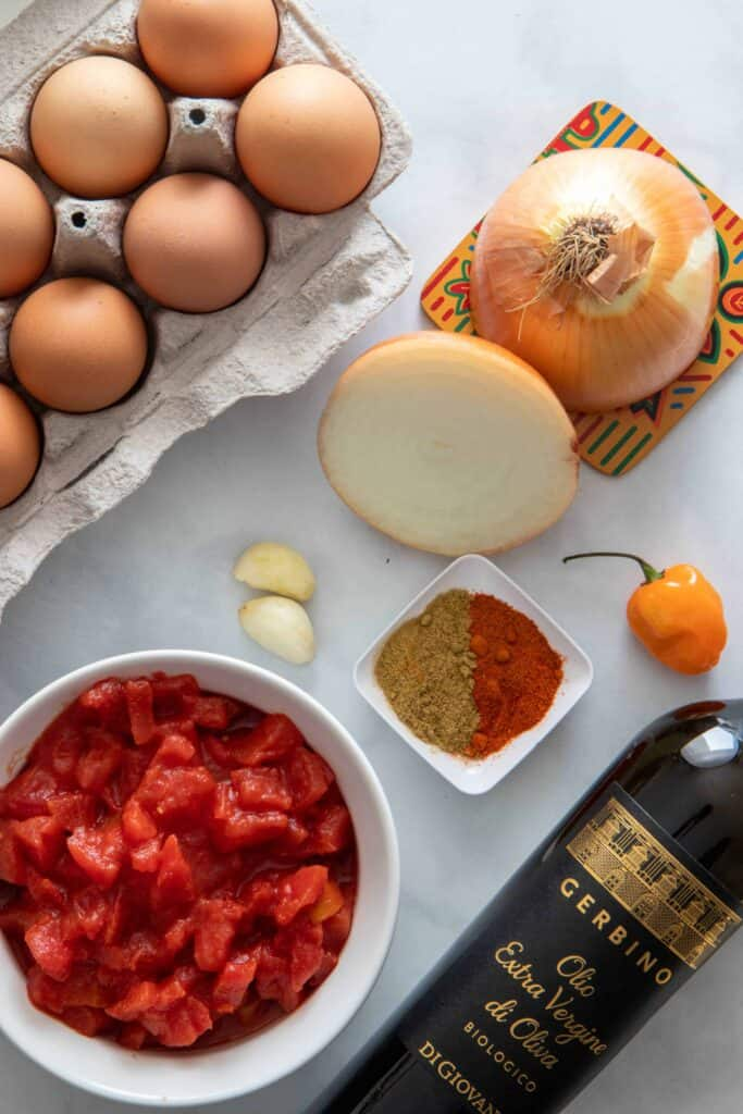 All the ingredients to make this recipe are mostly available in your pantry - shows canned tomatoes, spices, onions, eggs and olive oil