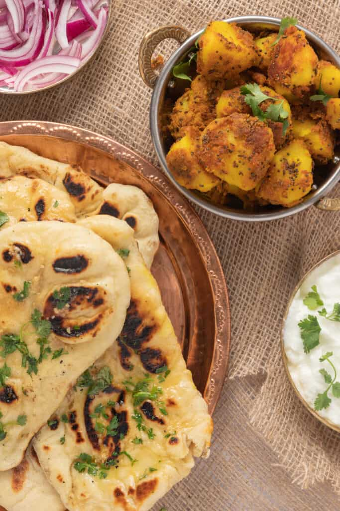Plate of naan next to potato curry and yogurt